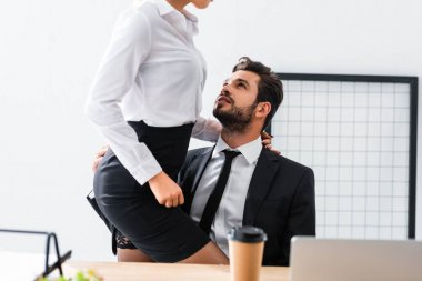 Cropped view of businesswoman touching sexy businessman at workplace