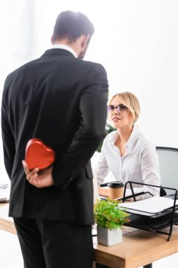 Selective focus of smiling secretary looking at businessman hiding gift