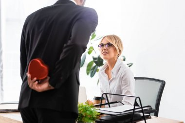 Selective focus of smiling businesswoman looking at colleague hiding gift