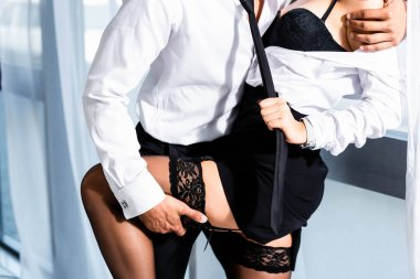 Cropped view of sexy secretary in stockings pulling businessman tie