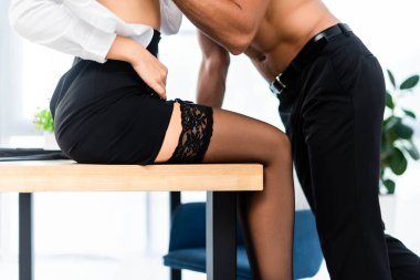 Cropped view of sexy businesswoman sitting on table by shirtless colleague