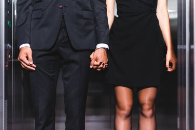 Cropped view of business couple holding hands in office elevator