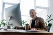 selektivní zaměření vousatý podnikatel při pohledu do kamery v blízkosti kávy jít a počítačový monitor v kanceláři