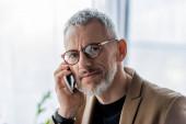 pohledný a vousatý podnikatel v brýlích mluví na smartphone