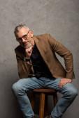 Fotografie glücklicher Geschäftsmann mit Brille, der in die Kamera blickt, während er auf grau sitzt