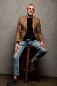 Fotografie Geschäftsmann mit Brille sitzt auf Hocker und blickt in Kamera auf grau