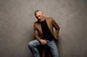 Fotografie Geschäftsmann in Jeans und Blazer sitzt auf einem Hocker und blickt in die Kamera