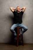 schöner Mann mit Tätowierungen sitzt auf einem Schemel auf grau