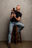 Fotografie glücklicher Mann mit Tätowierung zeigt mit dem Finger auf Smartphone mit leerem Bildschirm auf grau