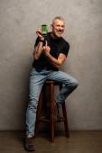 glücklicher Mann mit Tätowierung zeigt mit Finger auf Smartphone mit Medizin-App auf grau