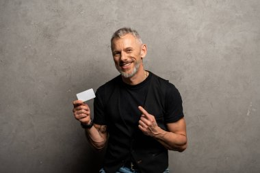 Happy businessman pointing with finger at blank card on grey stock vector
