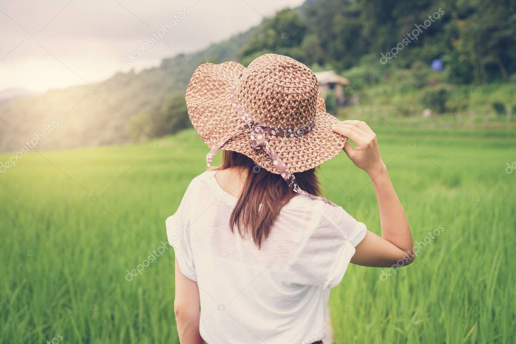 Woman traveler looking sunset at green rice terraces field