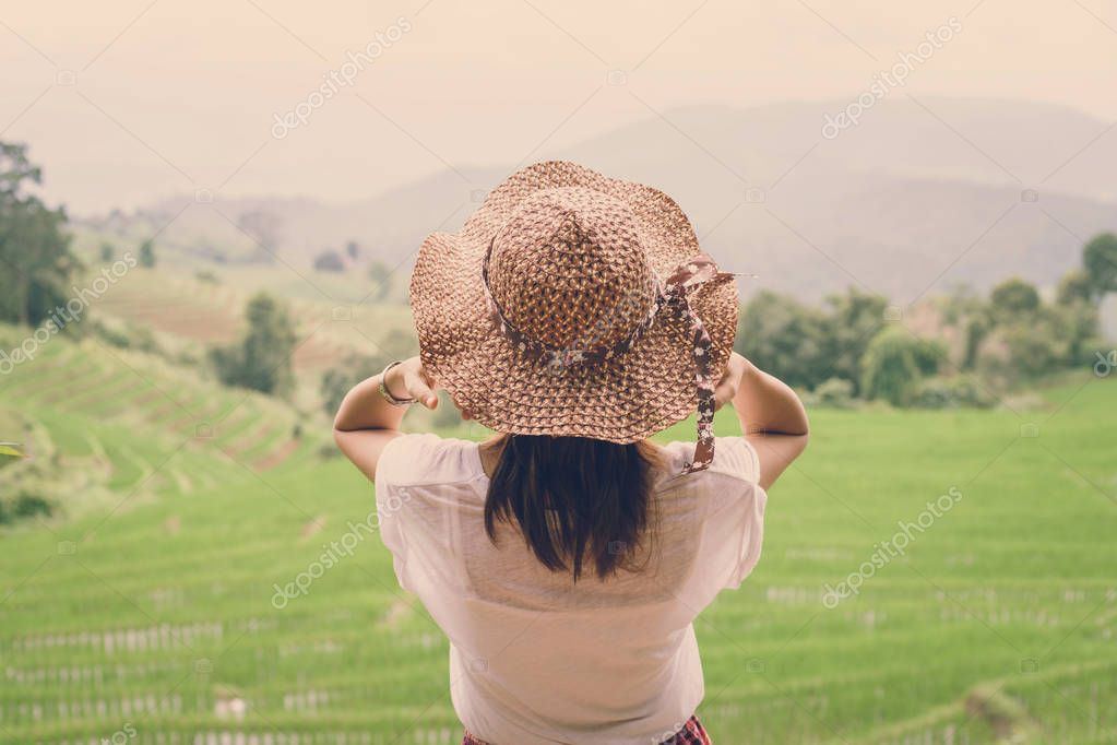 Woman traveler looking at green rice terraces field