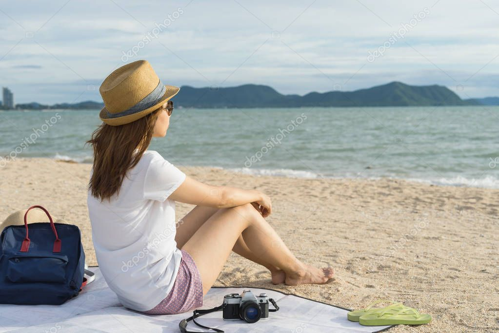 Female Traveler sitting on beach looking on sea waves