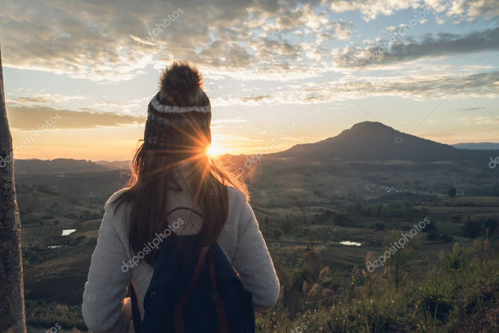 Cheering young woman traveler looking at sunrise
