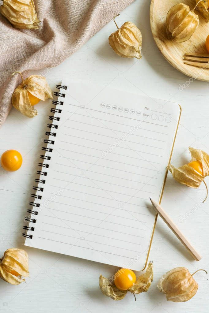 Cape gooseberry fruit and notepad on white wooden background