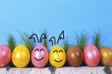 Easter eggs on wooden stick. Smiley face on easter eggs