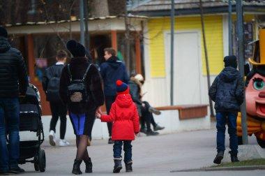 Arka plan bulanık. Çocuklu bir aile eğlence parkında yürüyor..