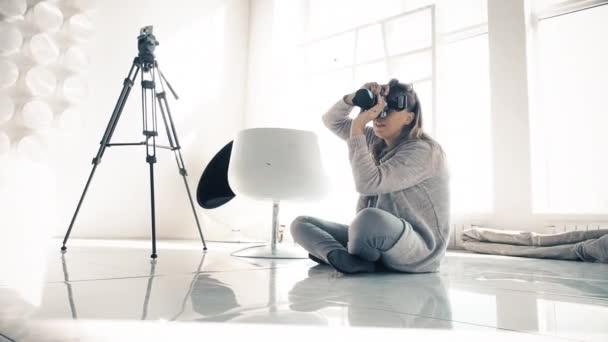 Eine Frau fotografiert auf einem weißen Spiegelboden sitzend, hinter ihr steht ein Stativ, ein weißer Stuhl. Umweg über den Schieberegler.