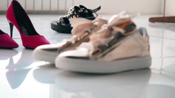 Red high-heeled shoes, gold sneakers with bows and black clogs with rivets stand on the white mirrored floor. Detour womens shoes on the slider