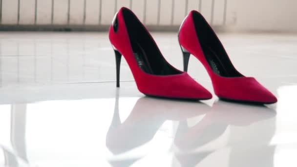 detour on the slider of red womens shoes standing on a white, mirrored floor