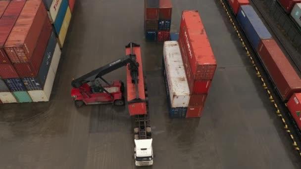 Pracovní nakladače na železničním terminálu: vyložení přepravního kontejneru z nákladního automobilu. Letecký průzkum.