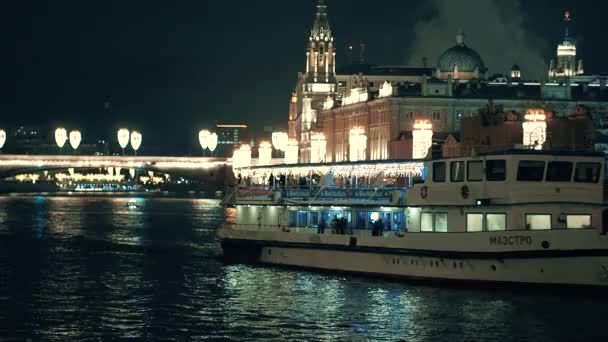 Ein von Neonlichtern beleuchtetes Schiff schwimmt nachts auf dem Fluss.