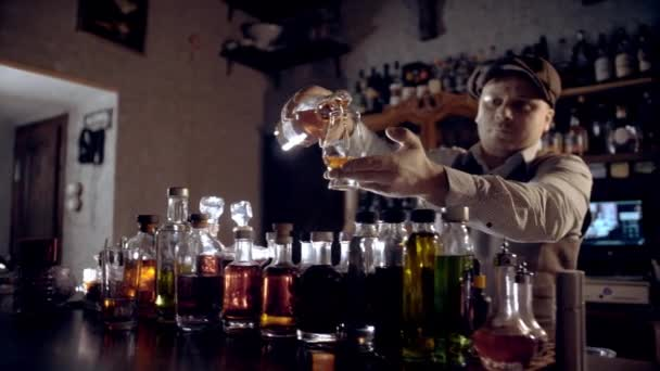 The bartender pours whiskey into a tasting glass (glencairn).  A bar counter in the speakeasy style. Dark scene, slow motion, camera movement.