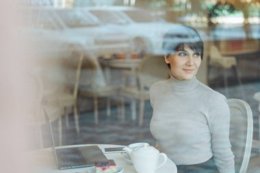Portrait of happy attractive smiling woman with shor hair wearing sitting in cafe looking through a window, view through glass