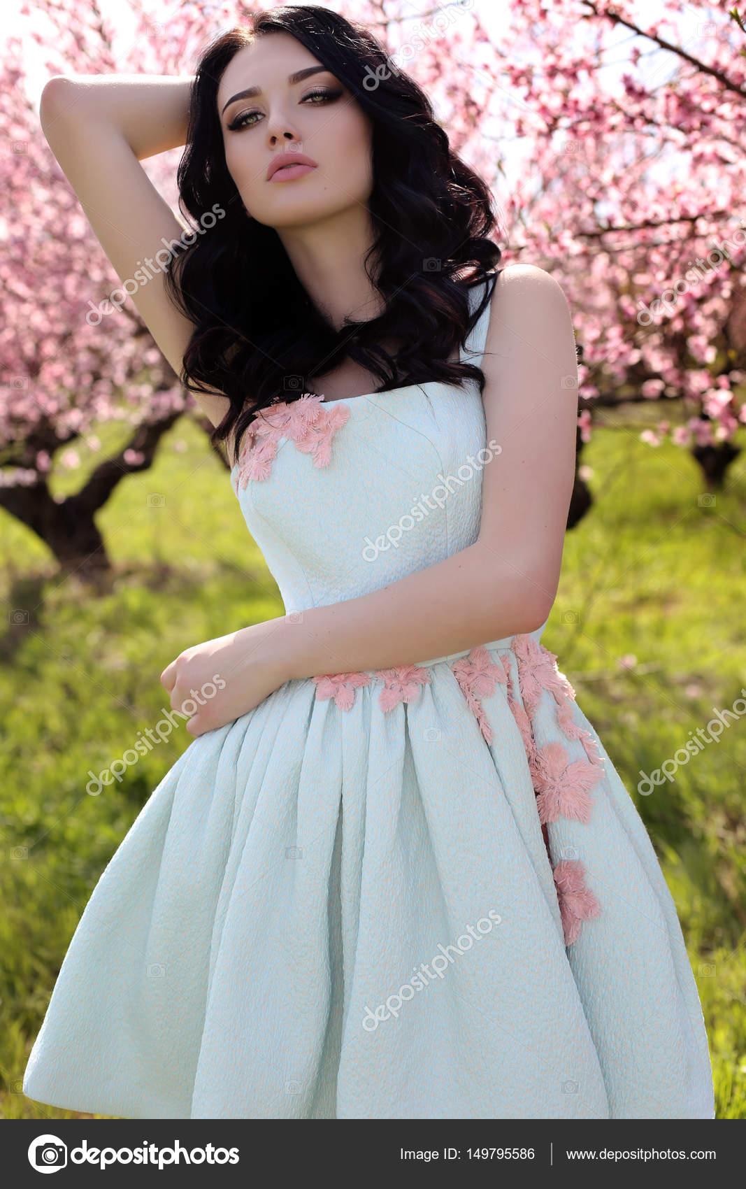 hermosa mujer joven en vestido elegante posando en el jardín, con ...