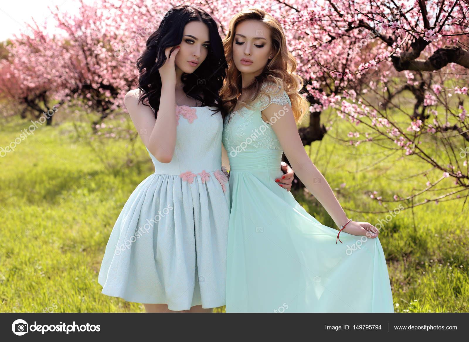 hermosas mujeres jóvenes en elegante vestido posando en el jardín ...