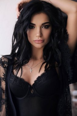 gorgeous young woman with dark hair in elegant lingerie