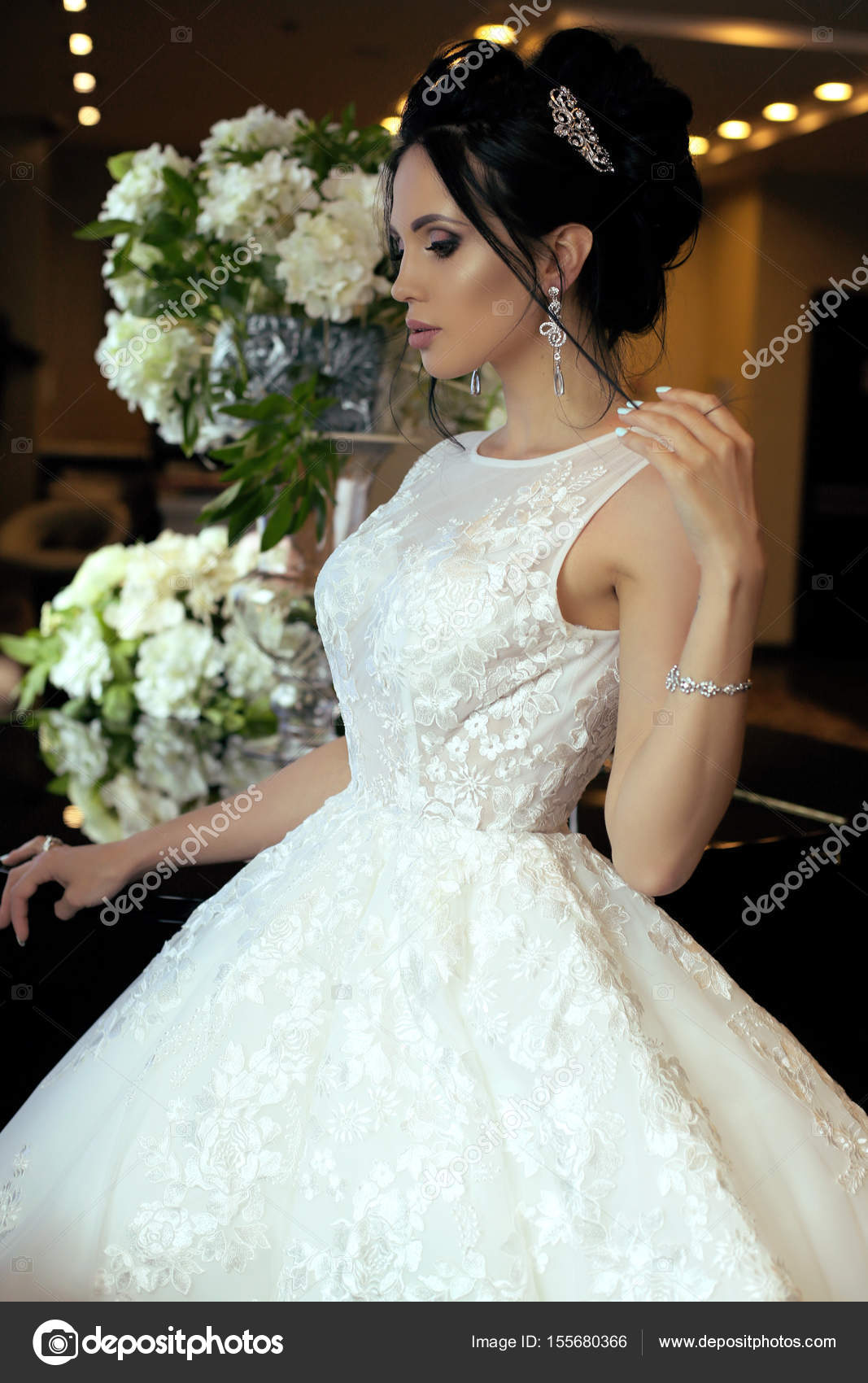 gorgeous bride with dark hair in luxurious wedding dress and acc