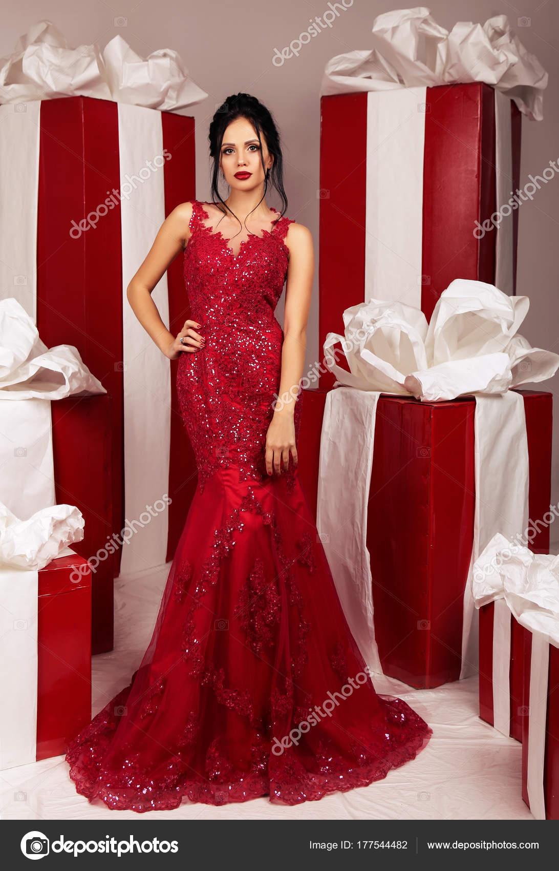 6f682ee503a8 mujer sexy con el pelo oscuro en el lujoso vestido posando junto a ...