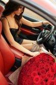 schöne Mädchen in elegantem Kleid posiert in luxuriösen Auto mit bo