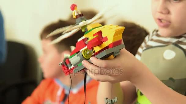 Dítě, kontrola práce jeho Lego vrtulník robota, Rusko