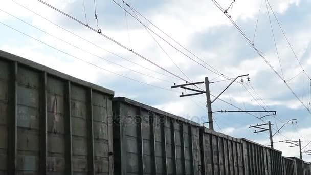 Jedoucí nákladní vlak a zamračená obloha