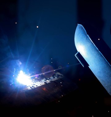 Close-up of welder working in workshop.