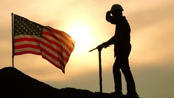 Worker with pickaxe on hill with waving USA flag on cloudy sky background