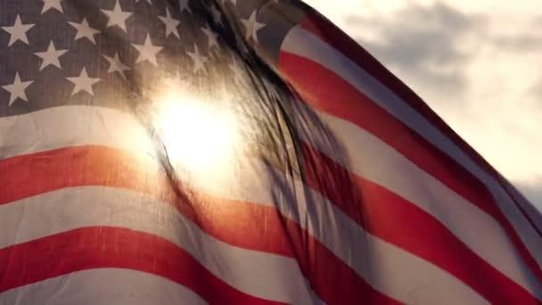 Waving USA flag on cloudy sky background