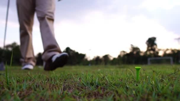 Muž hrající golf na louce