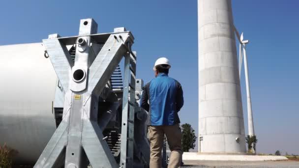 Inženýr s tvrdým kloboukem proti záběru větrné turbíny 4k
