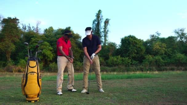Asijské muži hrát golf na louce
