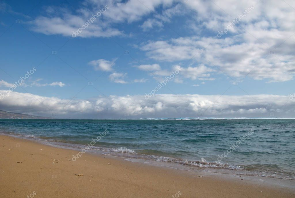 Beautiful sandy beach with clouds on the horizon on the island of Reunion