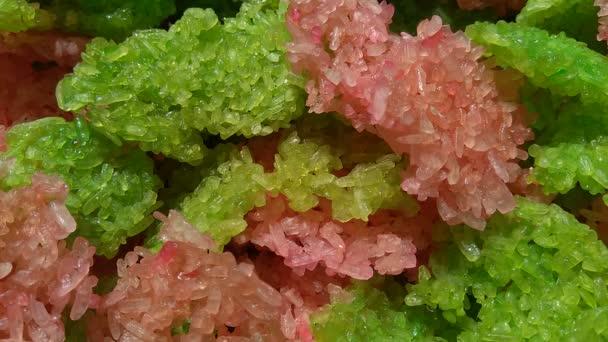 Raw green and pink rengginang. Rengginang je tradiční indonéská tlustá rýžová sušenka, vyrobená z vařené lepkavé rýže a kořeněná kořením.