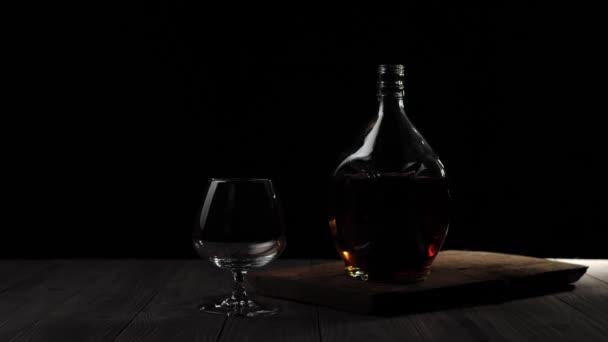 Luxusbrandy. Arany konyak egy kör alakú üvegben áll egy pohár mellett egy fa asztalon fekete háttér mellett. Fénysugár ragyog az asztalon, üveg vakít a fényben. Alkohol a szipogóban. 4k.