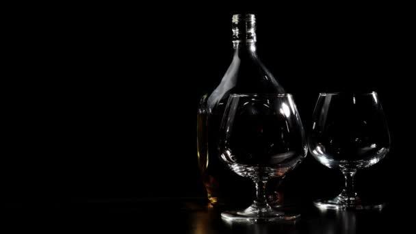 Luxusbrandy. Egy kerek üveg arany konyak és két pohár forog egy fából készült asztalon, üveg vakít a fényben. Brandy, konyak, snifter, binge. 4k.