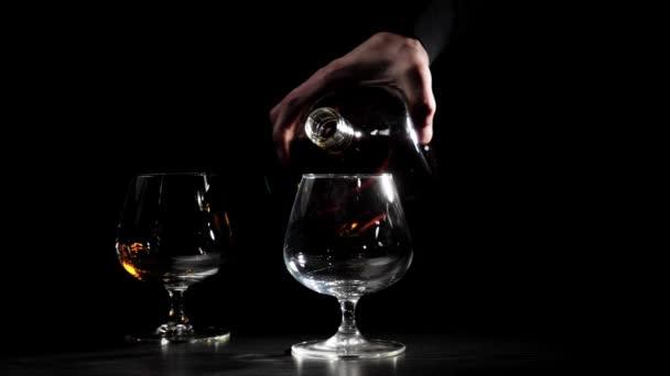 Luxusní brandy. Muž v černé košili nalije zlatý koňak z kulaté láhve do sklenice v popředí. Brandy, koňak, frňák, frňák. Zpomal. 4k.