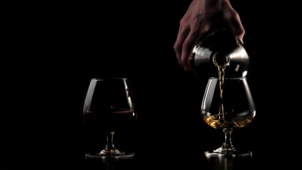 Luxusbrandy. A kéz arany konyakot önt egy kerek üvegből a fekete asztalon lévő két pohár egyikébe, fekete háttér mellett. Brandy, konyak, snifter, binge. Lassú mozgás. 4k.