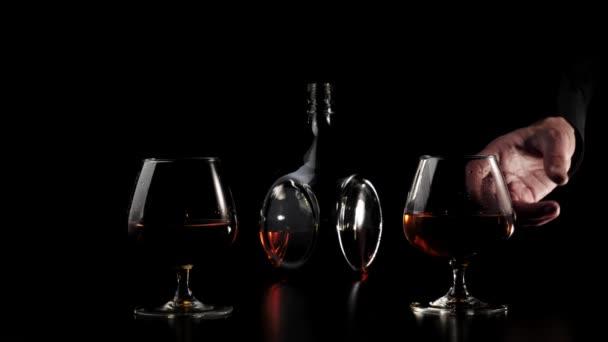 Luxusbrandy. Kéz fog egyet a két pohár arany konyakkal egy fekete asztal fekete háttér. Brandy, konyak, snifter, binge. Lassú mozgás. 4k.